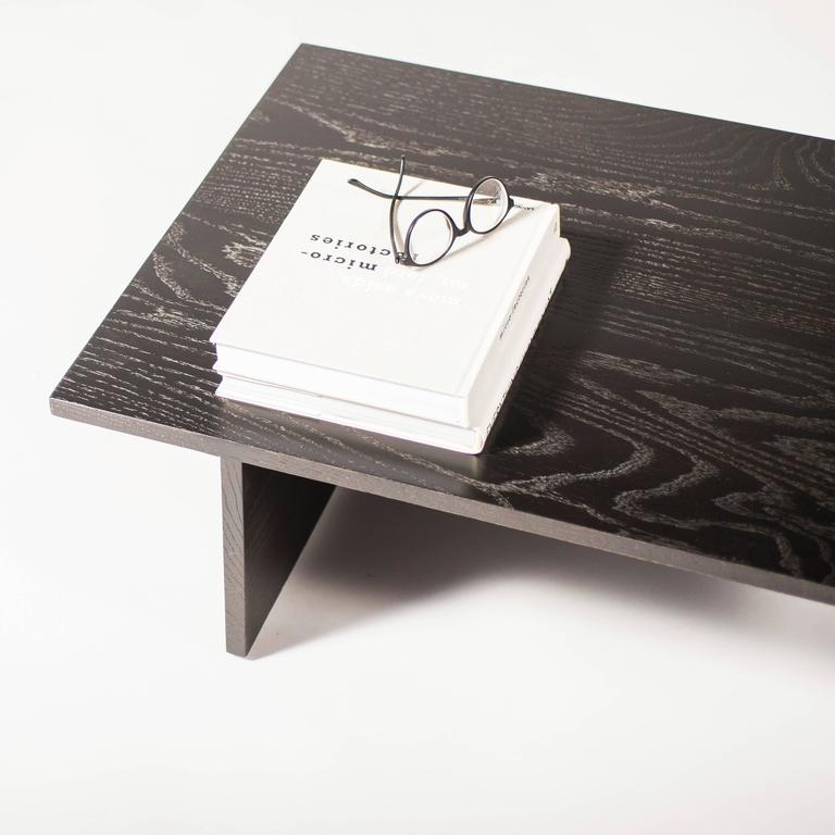 The coffee table focuses on the simplicity and natural beauty of wood. Whether natural or the black lacquered finish, the grain patterns of this contemporary oak tabletop seduce the mind and relax the body. Simple.