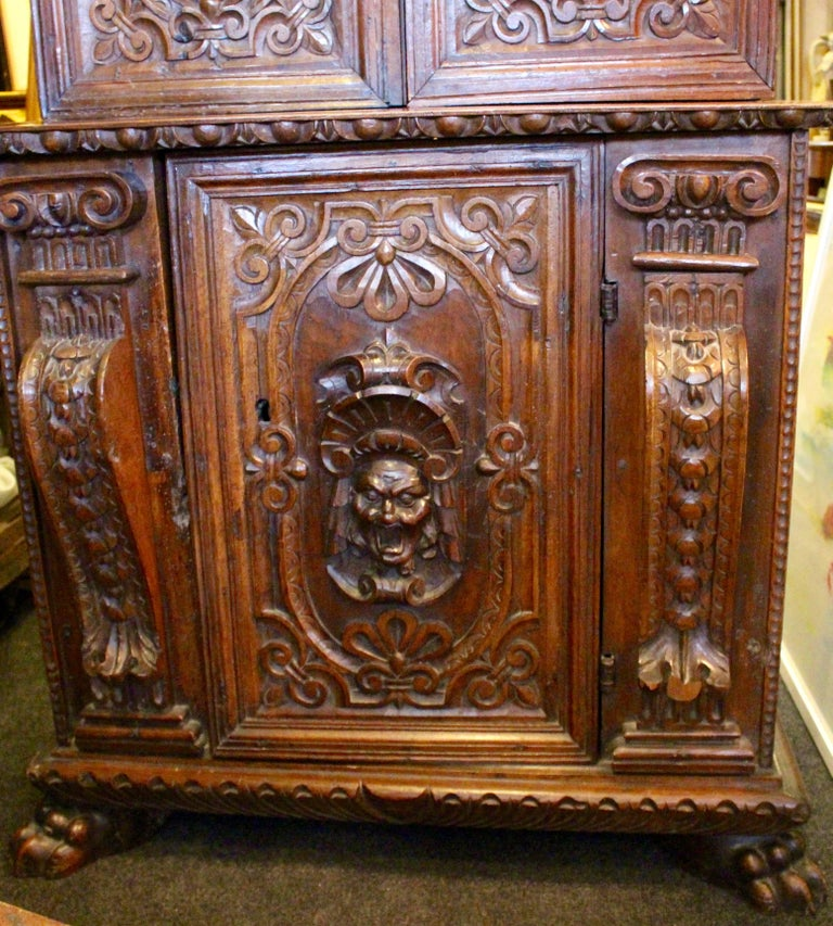 A stunning example of an early 17th century Italian cabinet. Heavily carved with egg and dart style pediment above upper cabinet with two beautifully carved doors, adorned with one happy and one sad face. Enclosing two shelves. The lower cabinet