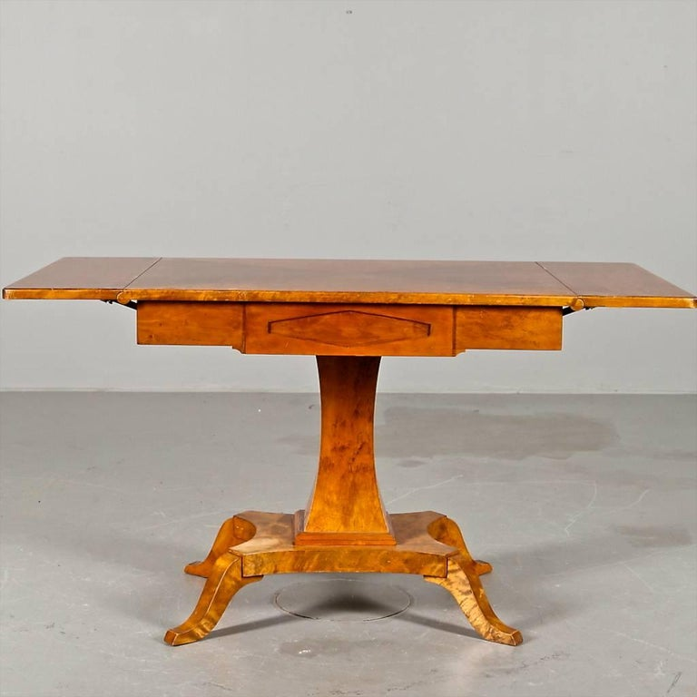 Unusual antique Swedish Biedermeier drop-leaf table in stunning quilted golden birch veneers with an inlaid carved central diamond on the front edge and four elegant curved feet.  Table wings are supported by pull out wooden arms underneath and the