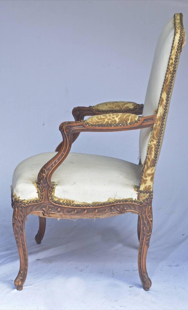 This is a Classic pair of original French oversized Rococo Bergere style armchairs from the late 19th century with carved Rococo arms and legs in a Classic rich brown muted French polish finish and with unusual delicately curved feet.  The extra