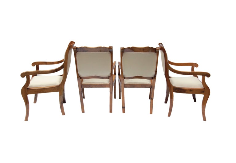 The rare set consists of four solid walnut armchairs from the Biedermeier period. The armchairs are newly upholstered and very well restored. The seat height is relatively high, so you can sit well at a table.