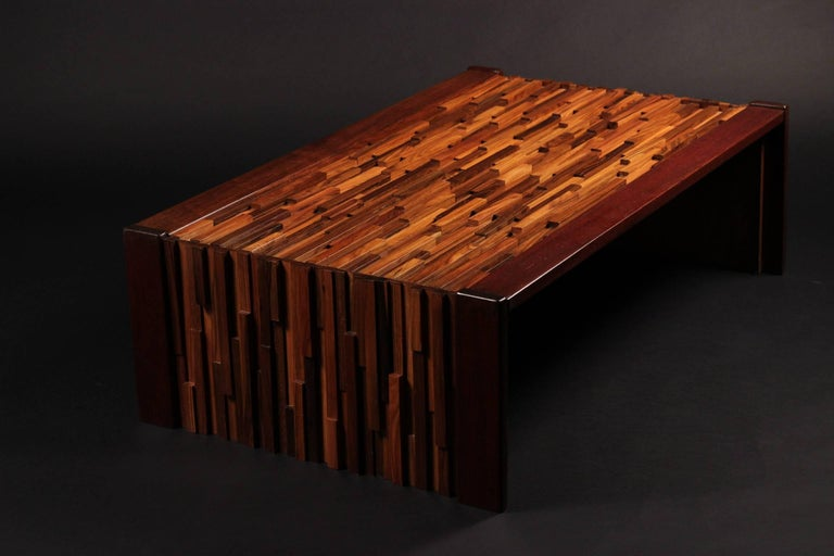 A Brazilian coffee or cocktail table with a wonderful sculptural quality. A relief of various tropical hardwoods in different heights and lengths to create a Brutalist effect, edged with Mahogany and fitted glass top. A table that comes to life when
