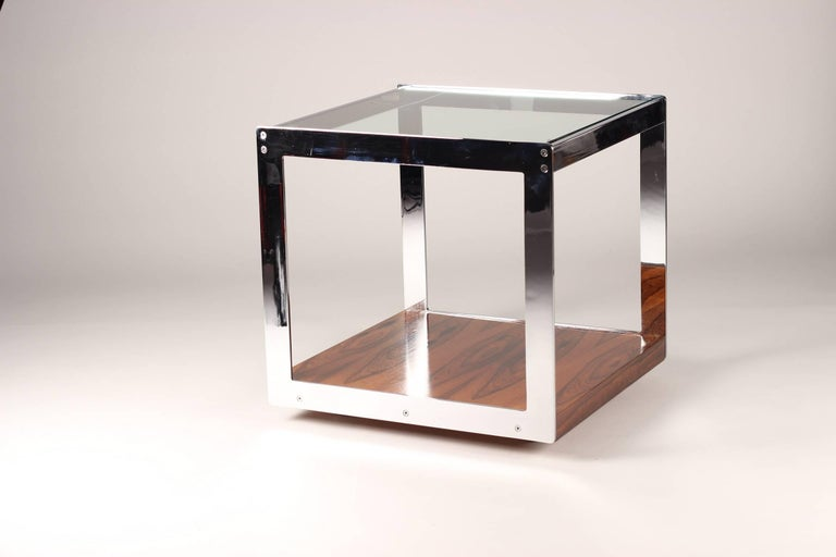 Designed by Richard Young for Merrow Associates and sold through Harrods of London in the 1970s. This rare Brazilian rosewood, chrome and glass table can be moved easily into and out of position with its concealed casters. The piece has a very