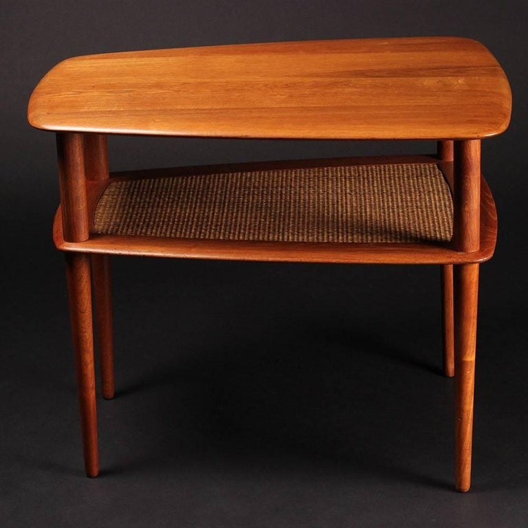 A restored and in good condition, solid teak and caned two-tiered end or side table. Bearing makers mark verso.