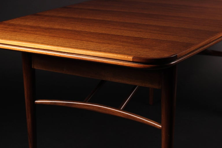 Sold at Heals of London this fine mahogany and teak extending dinning table, seats 6-8 with two extra leaves concealed beneath the table.  Measures: Width 180.0cm or 240.0cm with two extra leaves / height: 73.0cm / depth: 89.0cm  The table fully