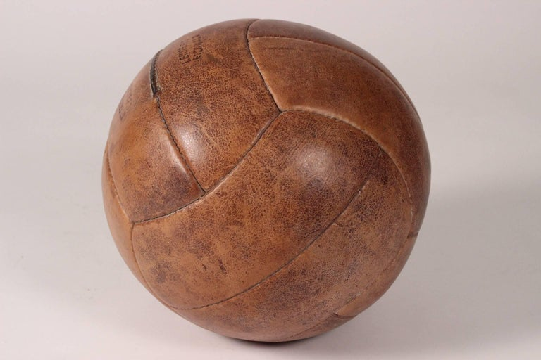 A wonderful vintage medicine ball, showing all the signs of wear of hard gym work through the years.