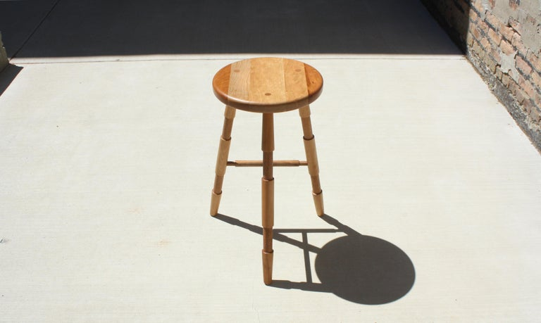Handmade in Chicago by Laylo Studio, this solid wood stool features lathe-turned and textured legs that are joined to the hand-carved seat using through wedged, tapered tenons - a tried and true method of joinery found in Windsor chairs - which are