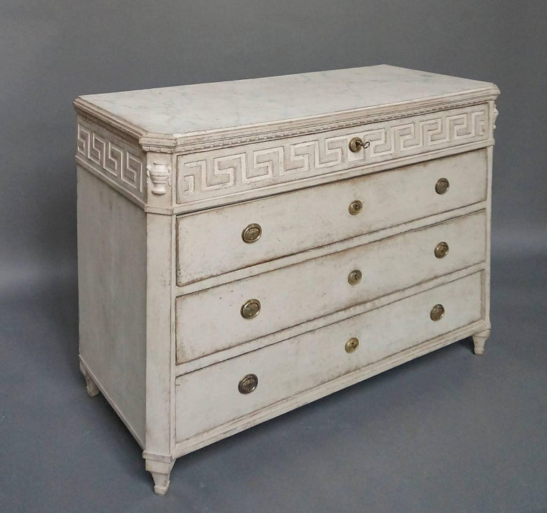 Swedish chest of drawers, circa 1860, with Greek key detail on the top drawer front and continuing around the sides. Canted corners with applied half-urns at the tops. Shaped top with painted marbling. Tapering square legs.
