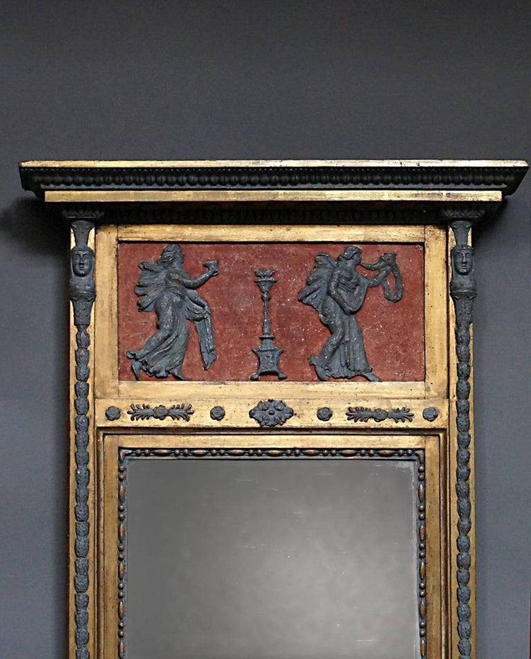 Period neoclassical mirror, Sweden, circa 1820, with original two-part mirror glass and back. The top frieze features two female figures in bas relief bearing symbols of victory. Below the mirror is a panel with sphinxes. The entire frame is