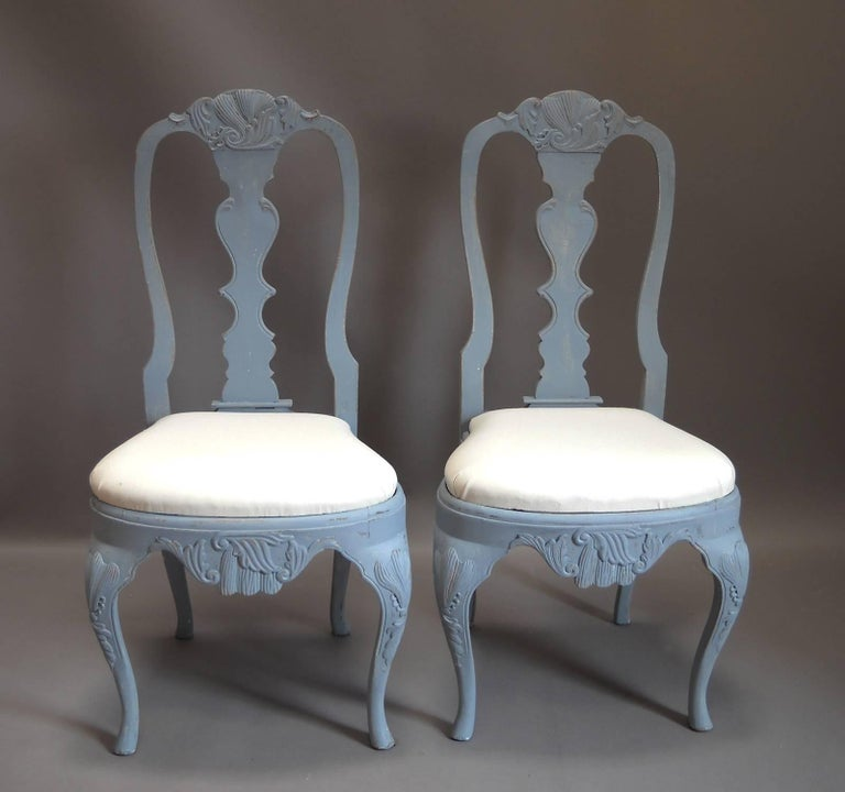 Set of eight dining chairs, Sweden, circa 1880, in the Rococo style with slip seats and elaborate carving.