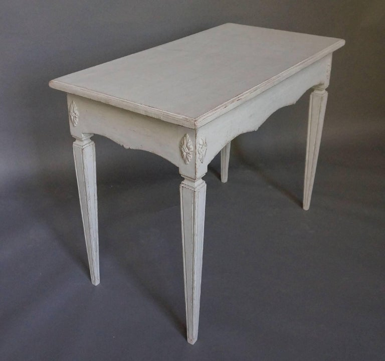 Freestanding table (finished on all sides) in the Gustavian Style, Sweden circa 1860, with scalloped apron. The tapering square legs have applied florets at the tops.