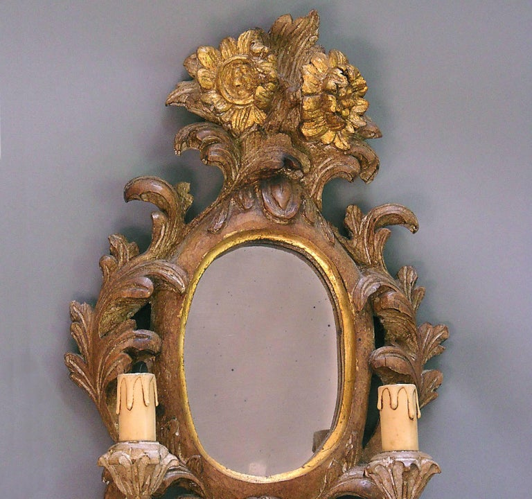 Carved wood and composition Danish sconce in the Rococo style with mirror and two candle holders. Highly decorative with blossom and fruit details.