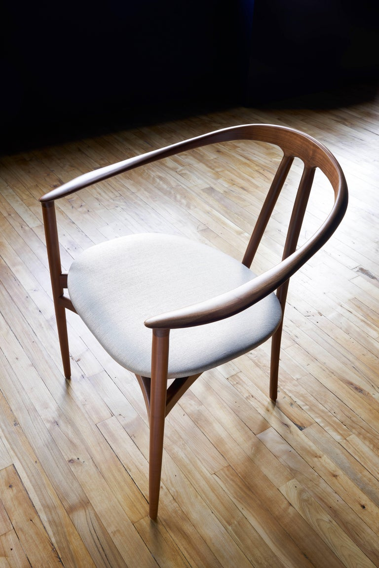 The sculptural armrest on this chair creates a striking silhouette that embraces the body. An upholstered seat provides a high level of comfort and a floating appearance. Tapered, splayed legs extend in an elegant curve from the top of the seat-back
