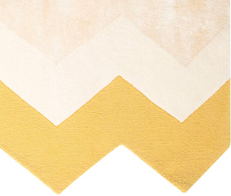 The Zuko rug features a fun chevron edge and matching print, in a soft, neutral color palette. Not another neutral to help ground a room. Rugs that make the room. Hand tufted rug made of a wool/viscose blend. Designed by Pieces.