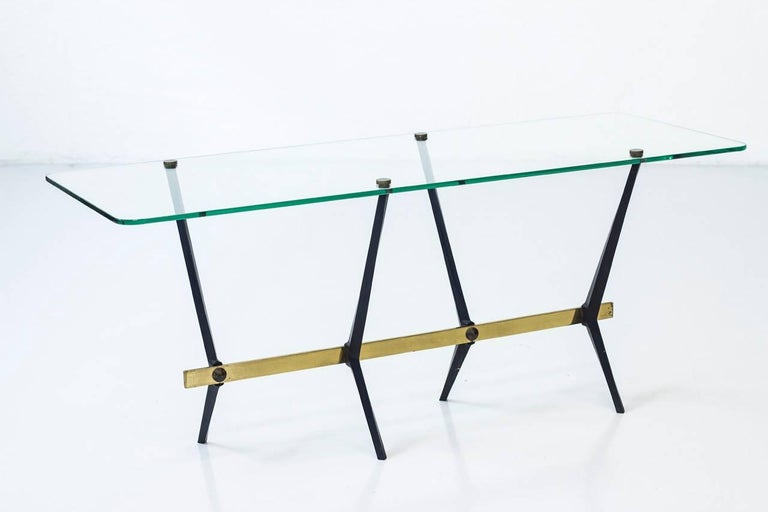 Sculptural coffee table designed by Angelo Ostuni most likely made in Italy during the 1950s. Thick glass top with rounded corner, supported by a brass and black lacquered metal frame/ legs. Very good condition with signs of wear and age related