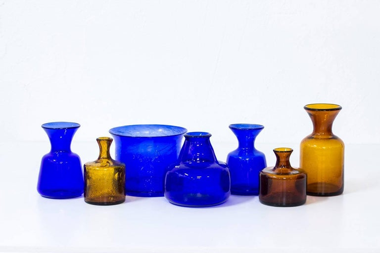 Group of seven glass vases designed by Erik Höglund, handblown at Boda glassworks in Sweden during the 1950s. Collection of blue and amber vases of various sizes and shapes, all with bubbles in the glass. Five of the vases are engraved with