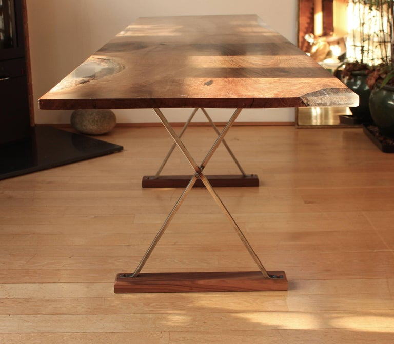 Ripple English walnut table with cross legs, the table is made from one piece of ripple English walnut with clear resin edge detail.  The raw steel cross legs are left unfinished with a wax coating. Walnut pegs hold the steel legs to the base