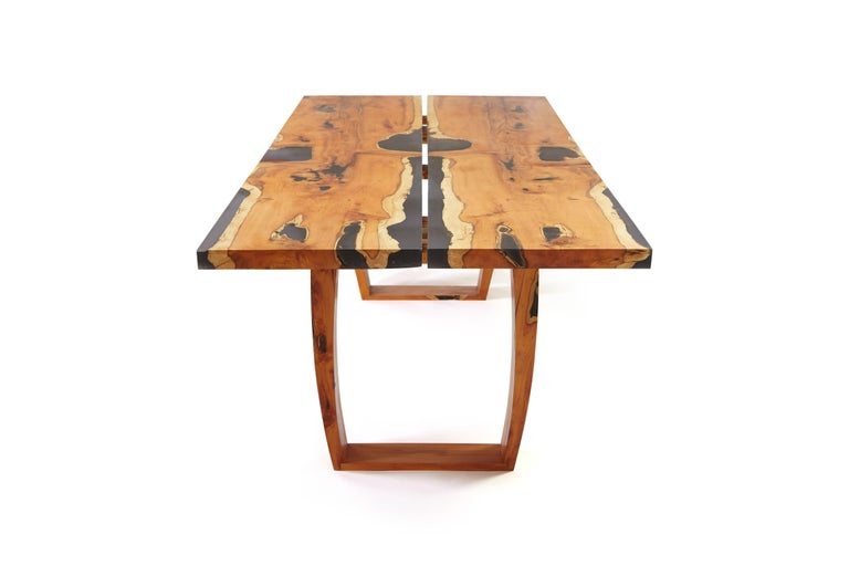 English Yew table; made from two slabs of mirror image /book matched yew with ebony tinted clear resin along the live edge. The table comes apart for moving. The making number is 165.  The top can be adjusted to remove the central gap.  Also a bit