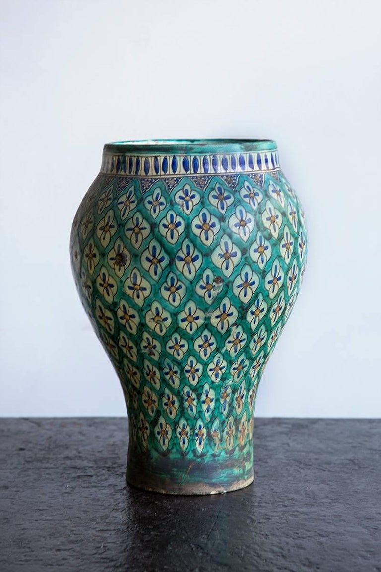 Baluster shaped earthenware, the turquoise trellis ground embellished over the glaze with hand-painted blue and white flowers, circa 1930.