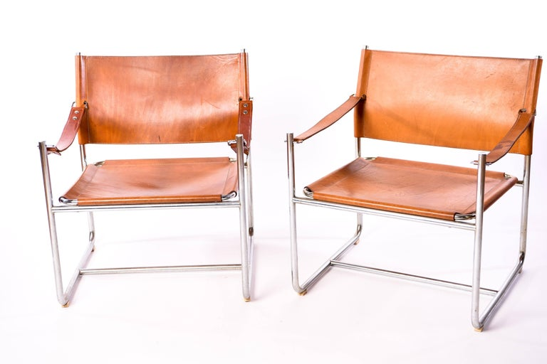 The 'Admiral' leather safari chair was designed by Karin Mobring for Ikea in the early 1970s. It is made from a chrome frame and patinated leather. This beautiful pair has a Classic midcentury appeal.