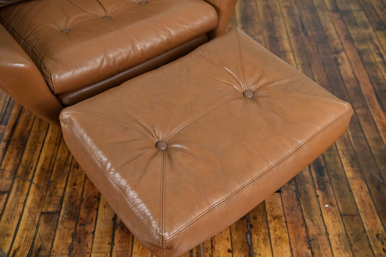 A beautiful Danish Mid-Century brown leather lounge chair and matching ottoman.