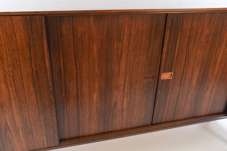 This sideboard by Arne Vodder features stunning rosewood with a beautiful grain and color. Small recessed handles adorn the sliding doors.