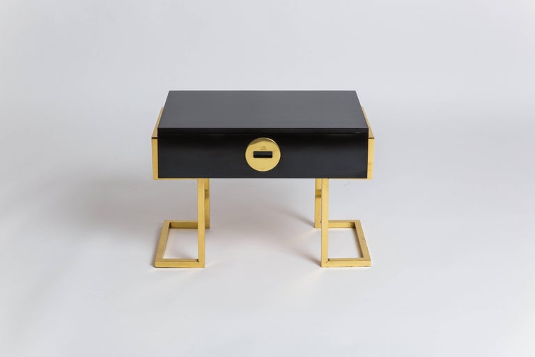 Romeo Rega pair of rare black laminate end or bedside tables with single drawers and architectural brass legs, Italy, 1970s. Each signed on manufacturer's brass roundel 'Romeo Rega/Made in Italy.'   These chic sculptural tables are in great original