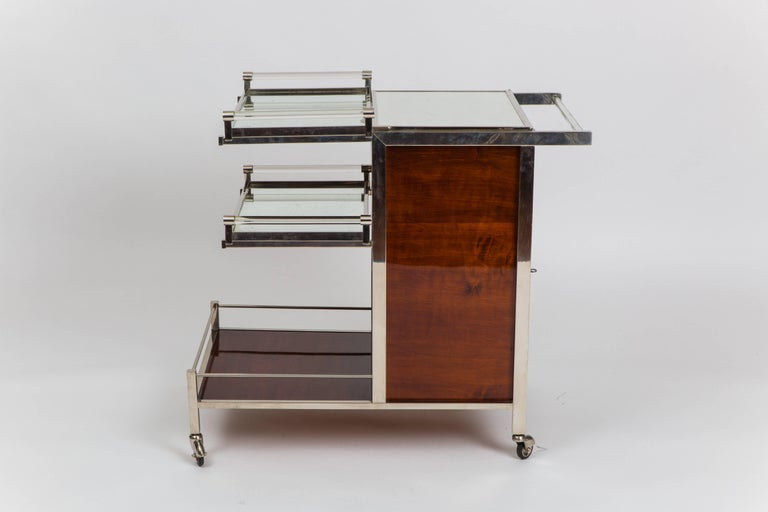 Jacques Adnet Art Deco palisander and chrome-plated metal bar cart with mirrored glass top which flips open to reveal compartment inside, side doors which hold cabinet storage for glasses and bottles, and 2 removable mirrored glass top trays with