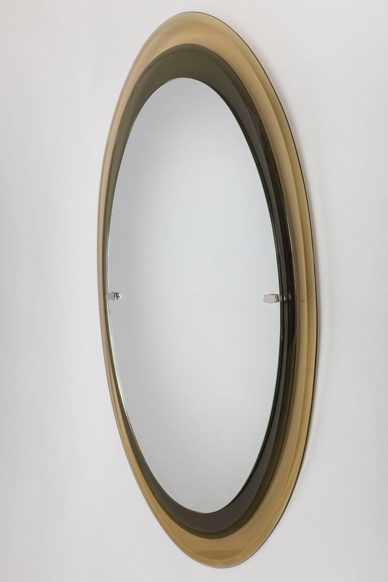 Two tiers of amber and dark gray, curved and bevelled glass framing original mirrored glass with nickel-plated metal mounts.  Literature: Quaderno Fontana Arte n°1, 1961, p. 26 Edoardo Paoli, Quaderni di Vitrum n°8, specchiere e specchi, p.