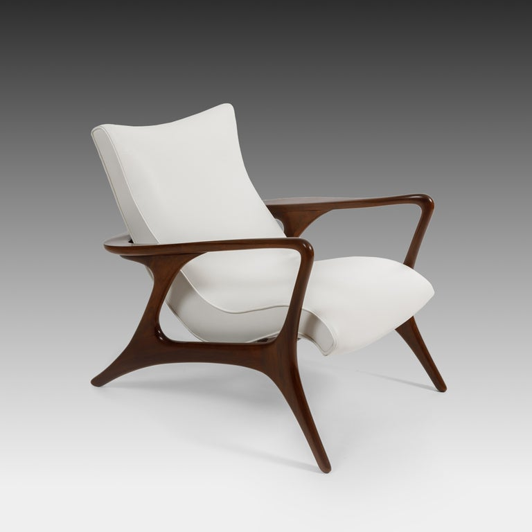 Early Vladimir Kagan for Kagan-Dreyfuss Inc. sculptural 'Contour' low back lounge chair in walnut frame and white leather upholstered padded seat, USA, 1950s.  This hallmark Kagan ergonomic design is meticulously crafted with sweeping lines and