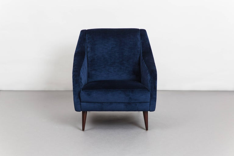 Pair of sculptural armchairs or lounge chairs in navy antiqued velvet upholstery with stained beech legs. These armchairs are an iconic Carlo De Carli design for Cassina with sleek architectural lines and great proportions for comfortable seating.
