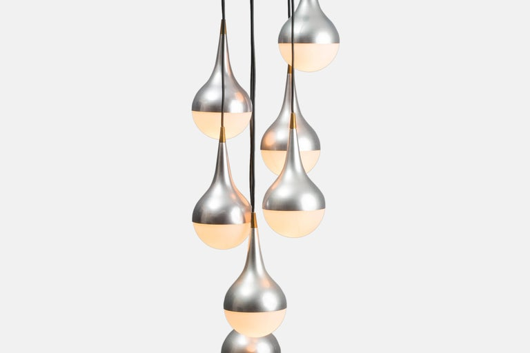 Seven frosted opaline glass balls held by brushed aluminum and brass fixings, suspended at different levels from black lacquered aluminum mount (adjustable). The contrast of the milky white shades, brushed aluminum and pop of brass elevate this