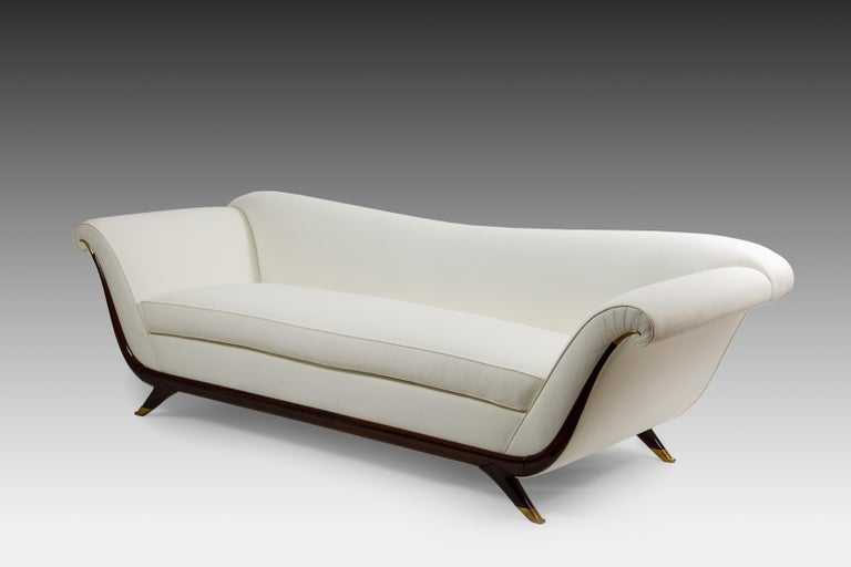 1940s Italian elegant long upholstered sofa with single seat cushion, lacquered wood and brass details, and splayed legs ending in brass sabots. This gondola-shaped sofa is contoured with sinuous lines in the scrolled arms, back and frame. Fully