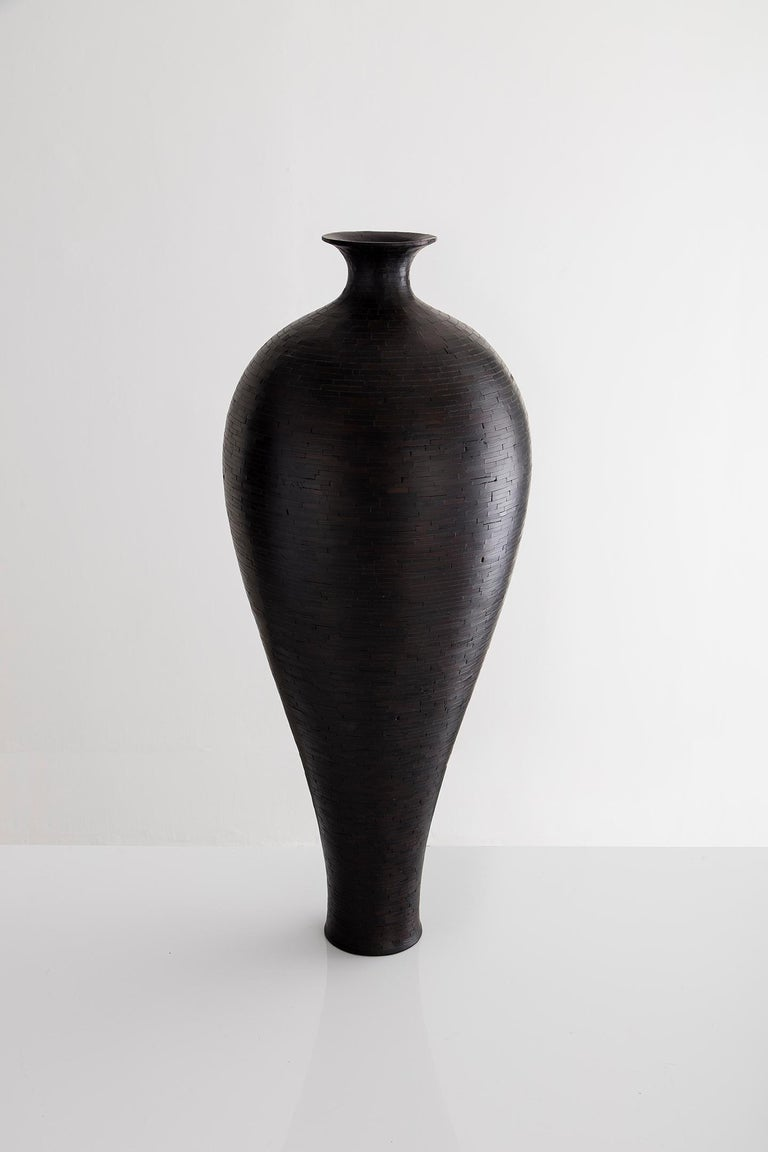 Part of Richard Haining's stacked collection, this vase was made using reclaimed Alaskan Cedar salvaged from a decommissioned NYC water tower. The wood's natural coloring is a very pale light blond. And although this vase is very dark in it's