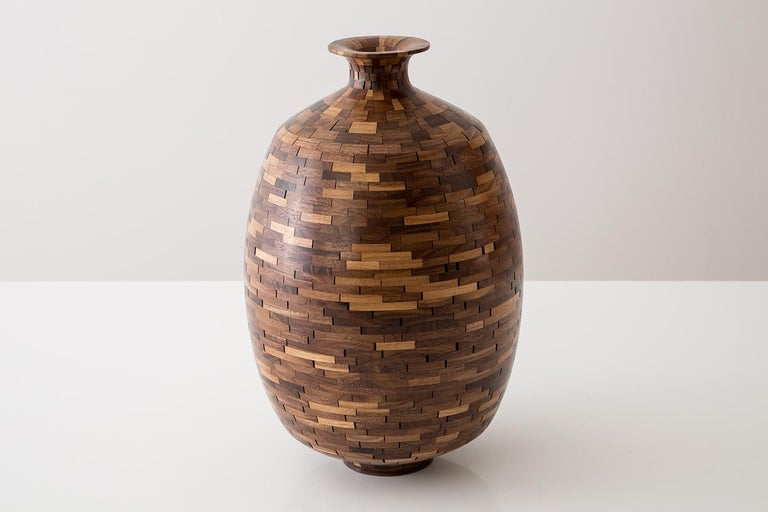 Part of Richard Haining's stacked collection, this vessel uses reclaimed walnut. The salvaged wood offcuts were sourced from a variety of local Brooklyn wood shops. The wood's natural coloring shows off tones primarily ranging from mid to dark