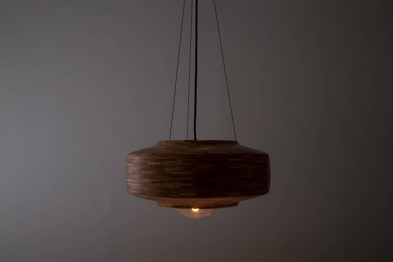 This saucer shaped pendant has not been turned on a lathe. Each shade is hand-built. Stacked piece by piece, 1/4