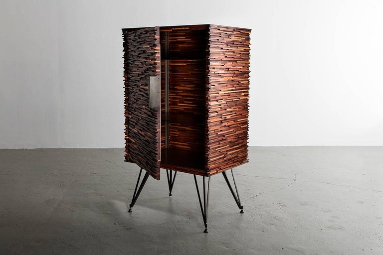 Part of Richard Haining's Stacked Collection, the carcass of this cabinet or dry bar was made using reclaimed mahogany, sapelle, and other tropical hardwoods with similar grain patterns. The base, shelving, and hardware are all made of steel. The