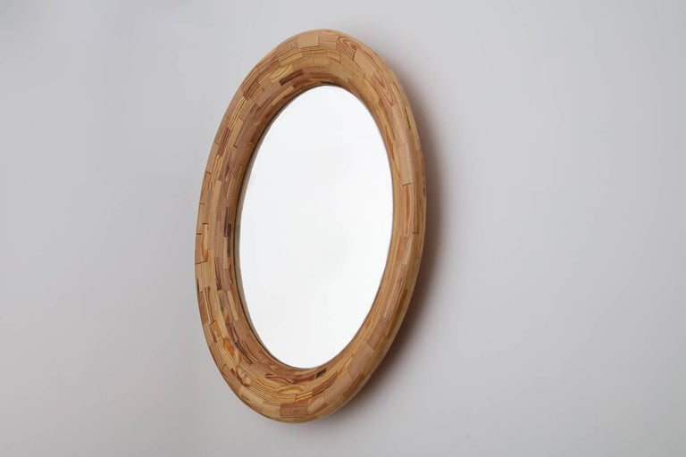 Part of Richard Haining's Stacked Collection, this 24 inch diameter round mirror has a 32-1/2 inch diameter frame made of reclaimed heart pine. The wood was salvaged offcuts from a gutted Brooklyn Brownstone's building joist. The wood's natural