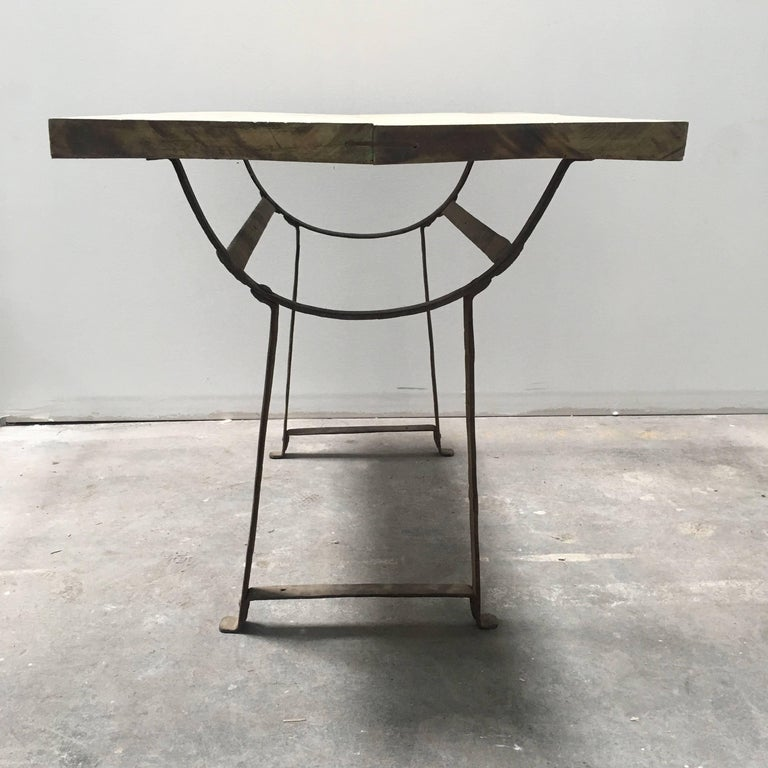 European trestle farm table from the 1800s with a metal base and a light wood tabletop.