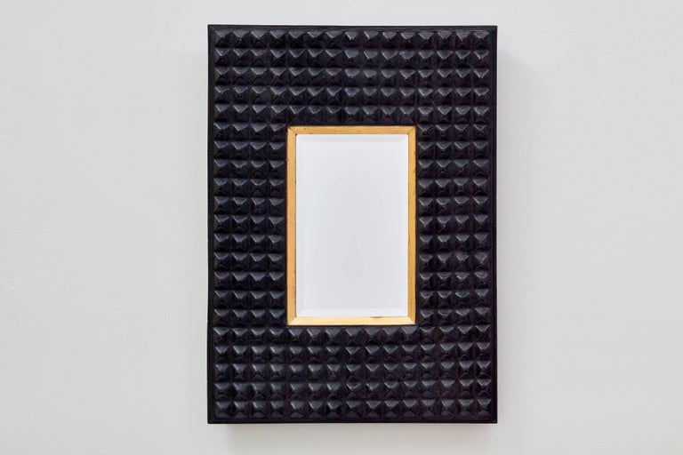 A perfectly imperfect rectangular shape, the studded surface and dark tone of the Ferarra mirror from Bark Frameworks evoke a tribal aesthetic. The mold for this mirror -- designed by Miguel Oks and Jared Bark -- was cast from a pressed tin