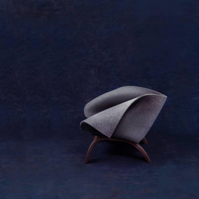 Babafelt is an easy chair made from thick natural wool felt. The felt sheet is cut and folded to make a cocoon-like space in which to sit, which responds to the occupants' movements and hugs them as they lean back. The wooden frame is made by