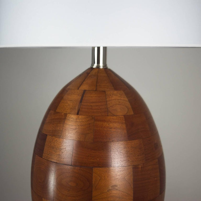 Egg shaped walnut lamp made of staved walnut blocks with clear satin finish. Professionally rewired with black silk cord and new lamp shade.   Shade measures 14
