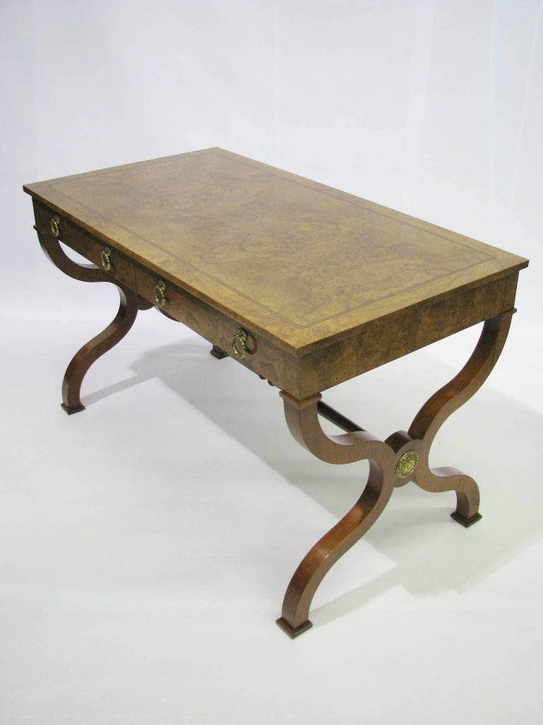 Beautiful and beautifully made Regency style writing desk or library table by Baker Furniture. Burl walnut veneers cover the top and all four sides of the case. The legs are solid hardwood. A contrasting band of ebonized stringing details the top's