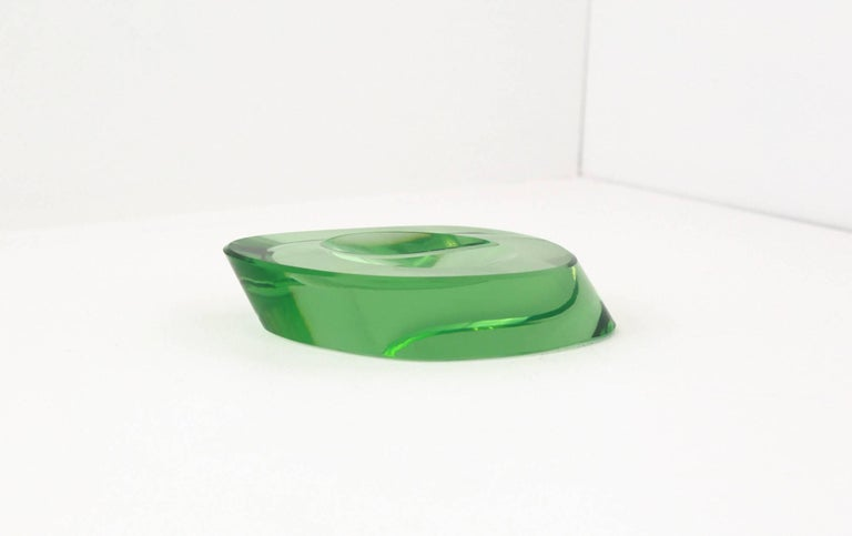 A beautiful example of an early offering from Fontana Arte, Murano. Elliptical in shape, with cut, canted sides, this dish has a concave circular cut-out on its surface. This dish has a wonderful depth of colour and clarity that is synonymous with