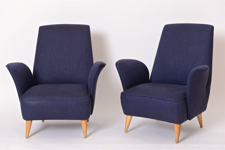 A wonderful pair of 1950s Italian lounge chairs in the manner of Nino Zoncada. These curvaceous Italian armchairs have been completely restored and re-upholstered in a luxurious navy blue linen fabric from Holly Hunt. Sitting on tapered maple legs,