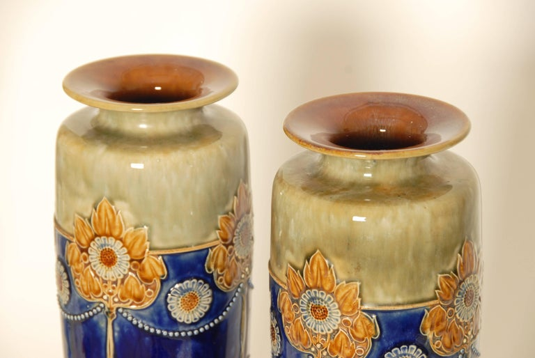 A pair of large and impressive Art Nouveau Royal Doulton stoneware vases. Hand-painted with stylized flowers, factory marks and numbered 6621 on the bases. Measure: 14.5 inches high.