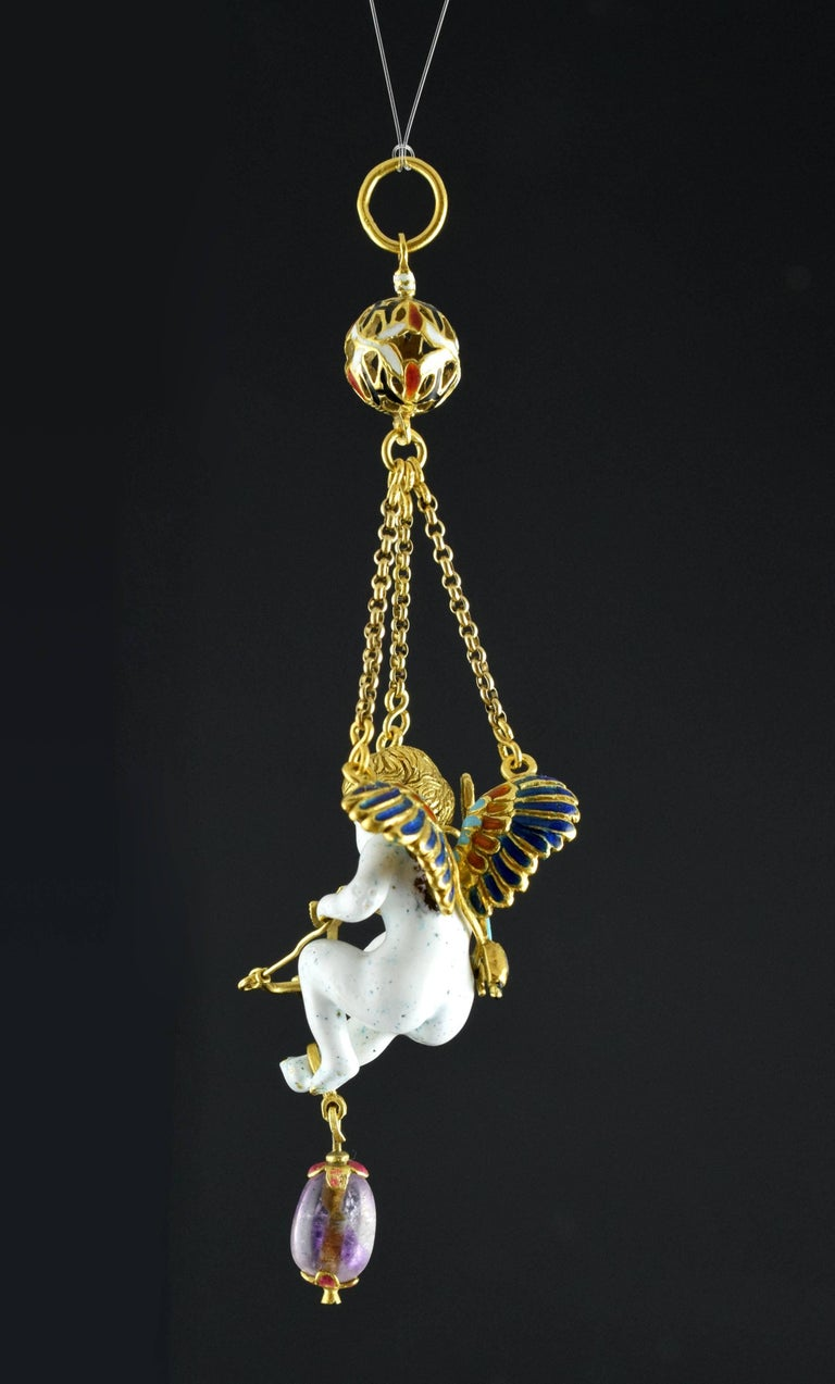 The white human figurine is suspended in the air thanks to three gold chains, which are joined in a perforated ball decorated with red, white and black enamels, from which arises the ring from which the pendant would be hung around the neck. The