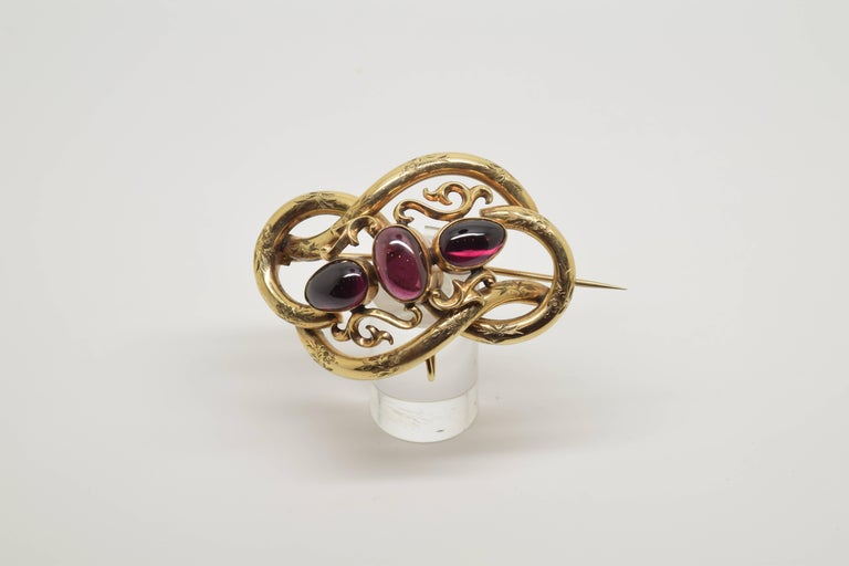 Lady's brooch made in 14-karat gold formed by a base shape arranged in a knot, leaving waves in the outer profile, with the surface decorated with fine vegetal forms of leaves and flowers. In the centre a few simple plant scrolls have been arranged,