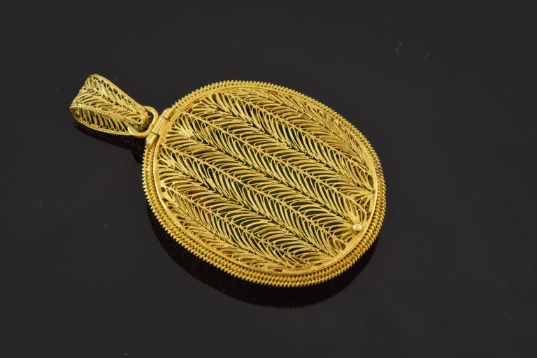 Empire style locket, circa 1800. 18-karat gold and enamel. Beautiful locket entirely made in 18-karat gold filigree, composing a light and open structure that combines in its decoration synthesized vegetal motifs, florets, counters and striated