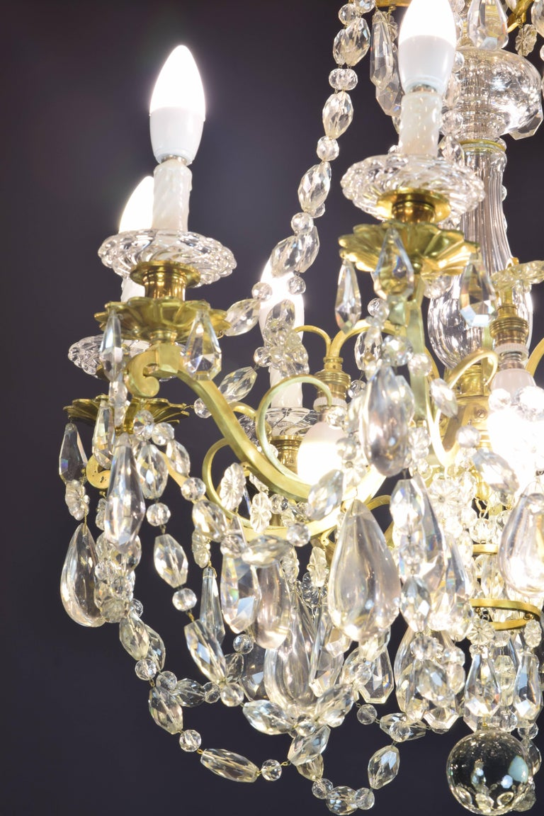 Baccarat signed chandelier. Glass and gilt bronze, 19th century. Gilt bronze and transparent glass chandelier with eight lights. The upper part has a series of curved sticks from which hang some glass beads in various shapes (flower, tear). The
